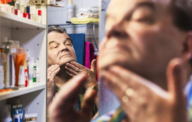 Kotoa, kylpyhuoneen kaapin hyllyiltä löytyvät tuotteet Hannu Luostarisen ihonhoitoon.