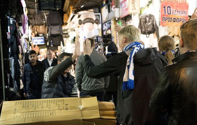 Monet paikalliset tervehtivät laulavia Suomi-faneja.