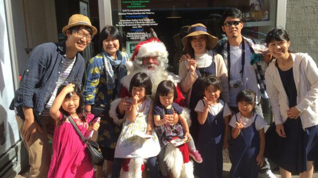 Joulupukki poseeraa turistien kanssa Hietalahdenkadun toimistonsa edessä.