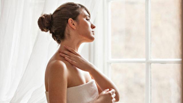 Nainen hoitamassa ihoaan suihkun jälkeen