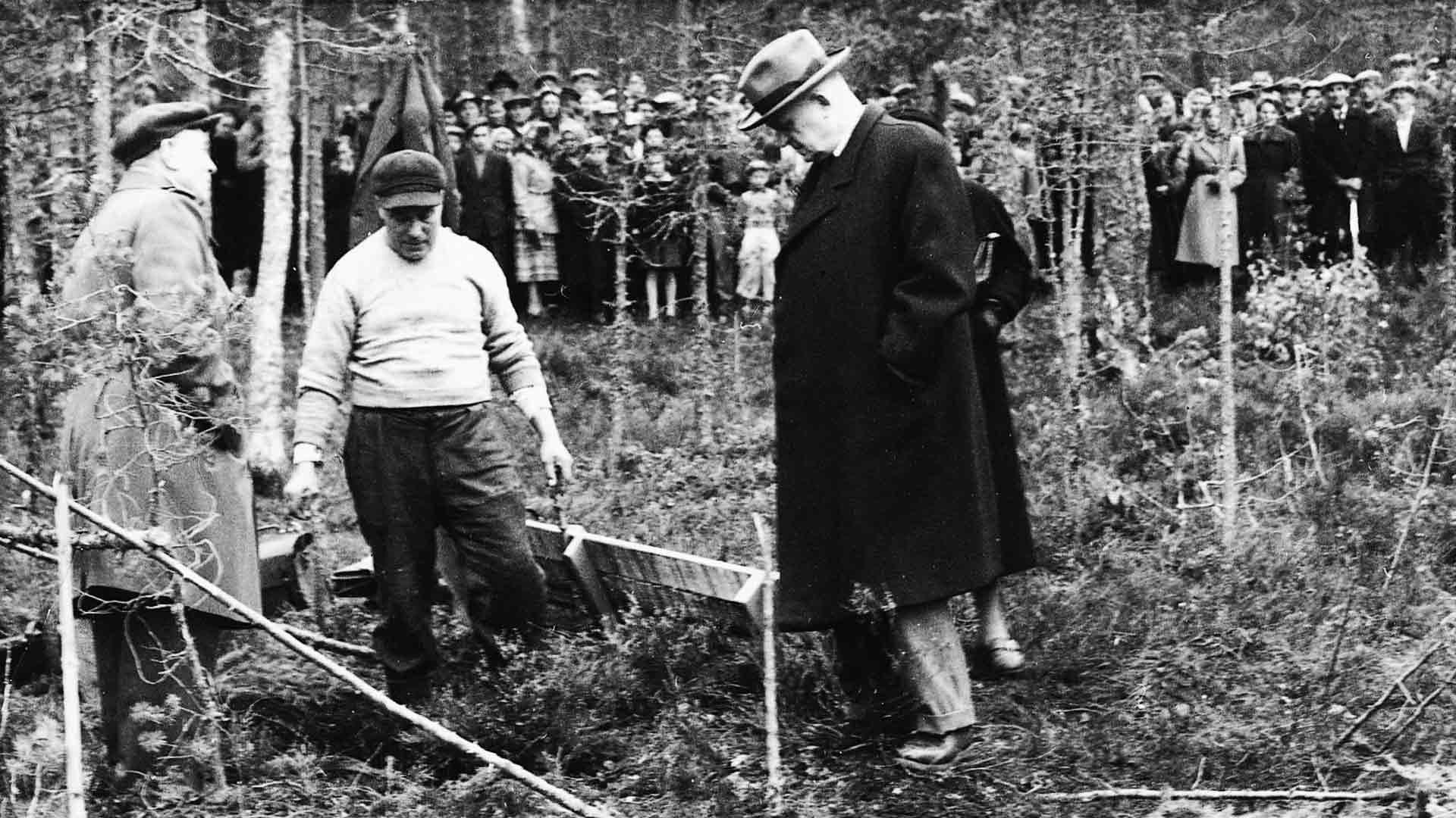 Isojoen lääninlääkäri Onni Hokkanen ja päätutkija Axel Skogman tutkivat suohautaa. Väkijoukko seuraa.