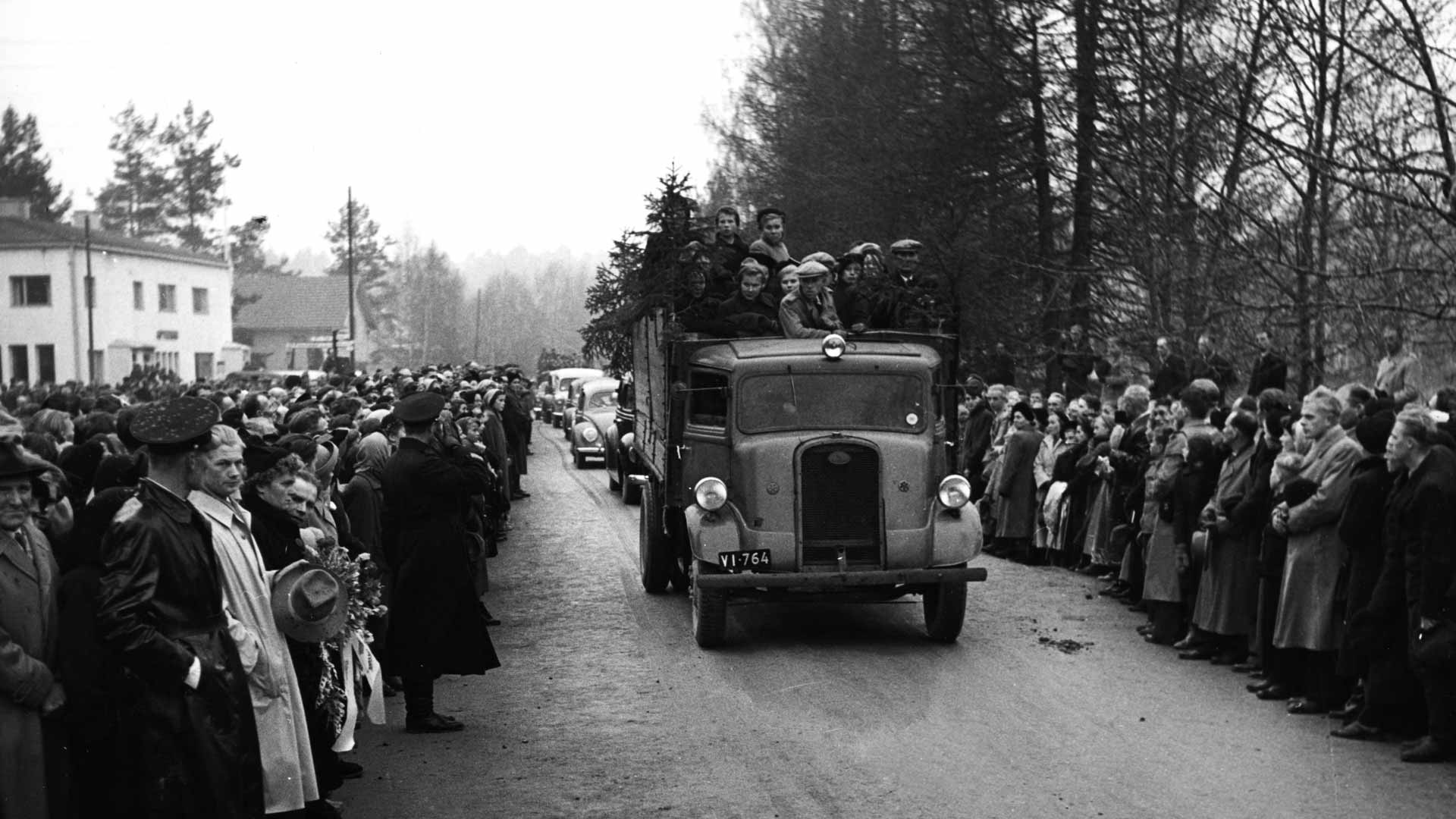 Hautajaiset keräsivät väkeä tienvarsille. Autosaattue kulki Isojoella harmaana lokakuisena päivänä.