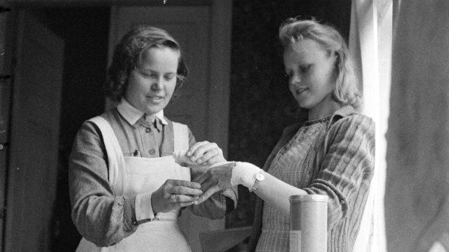 Teiden varsille oli sopiviin kohtiin järjestetty siirtolaisille lääkintähuoltoasemia. Lääkintälotta sitoo loukkaantuneen käden Parikkalassa kesällä 1944.