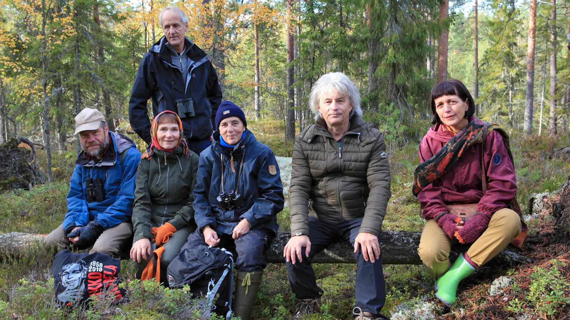 Matti Salminen katsoo takaa, kun Jukka Ruuhijärvi, Maritta Liedenpohja, Anneli Leivo, Juha Torvinen ja Eeva Saarela istuvat levähdyspaikalla.