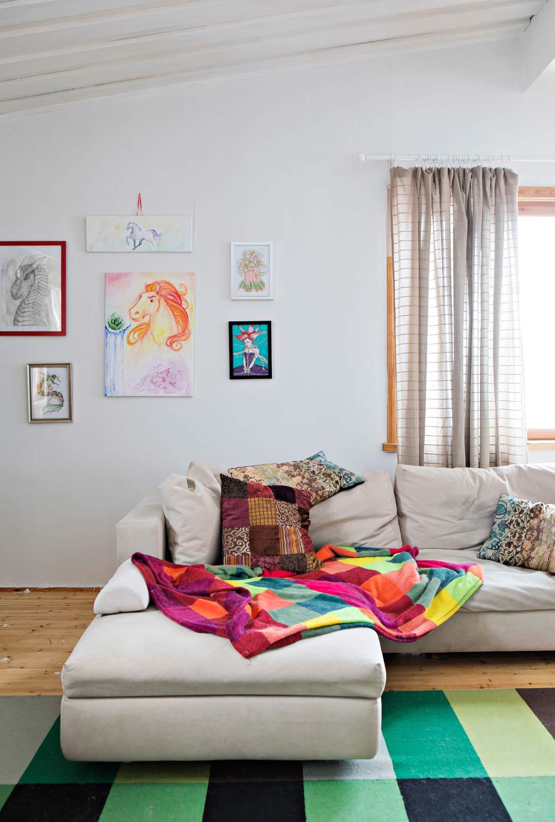 Värikkäät tekstiilit raikastavat olohuoneen. Seinillä on tyttären maalaamaa taidetta.