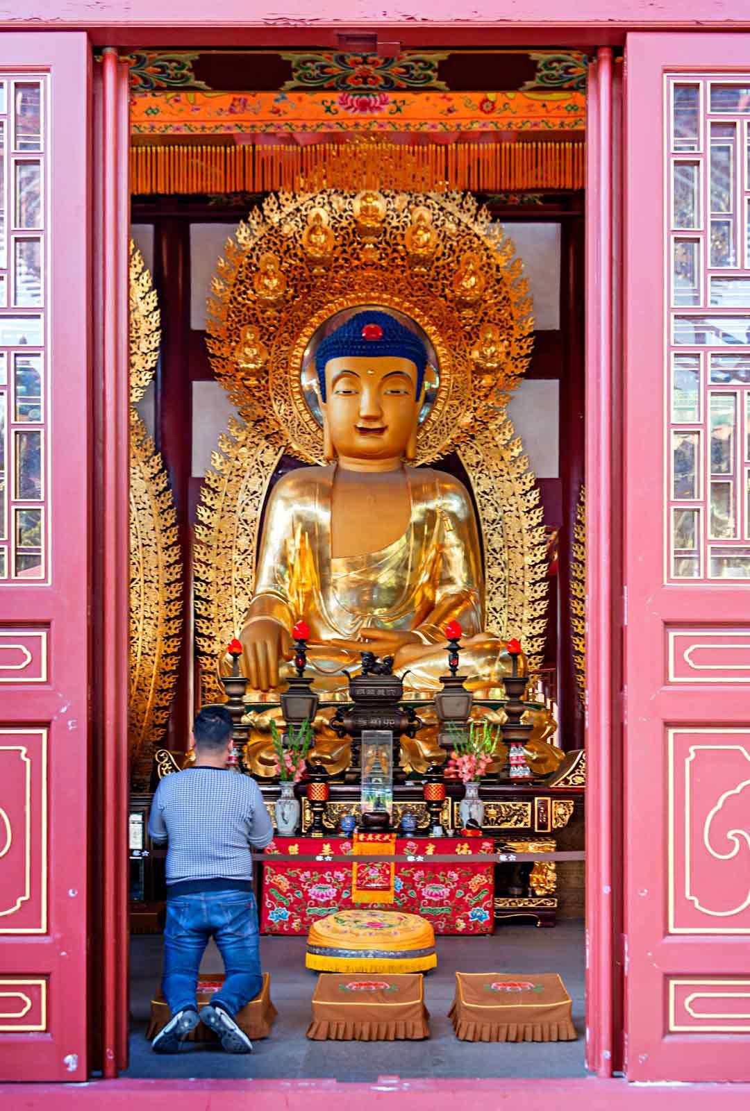 Paikalliset polvistuvat rukoilemaan kolmen valtavan Buddha-patsaan eteen. Ne edustavat mennyttä, nykyistä ja tulevaa.