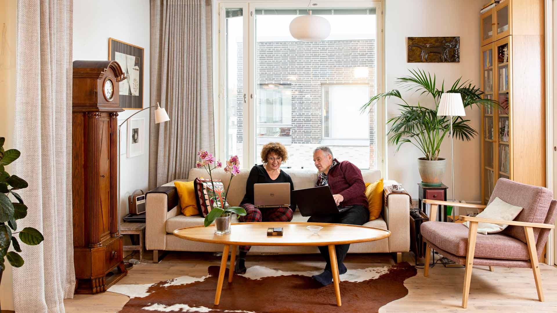 Olohuoneen sanomalehtikatsaus: Anneli ja Ari lukevat aamun sanomalehden aina läppäreiltään.