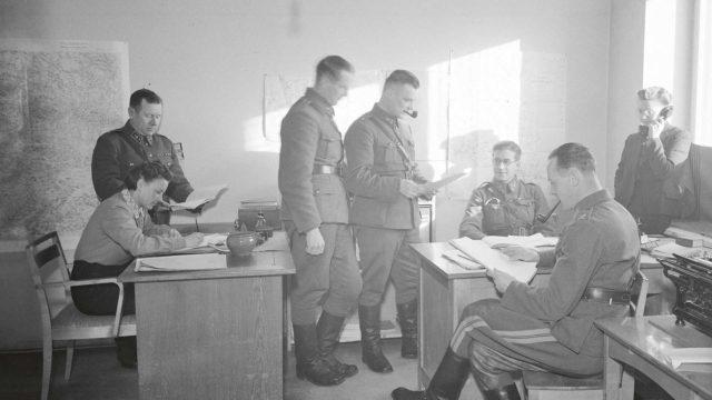 """Valvontaosaston Mikkelin alatoimiston väki asettui poseeraamaan valokuvaajalle """"työn touhussa"""". Silmälasipäinen Pentti Ignatius istuu työpöytänsä takana, piippusuinen Gösta Falck seisoo vieressä."""