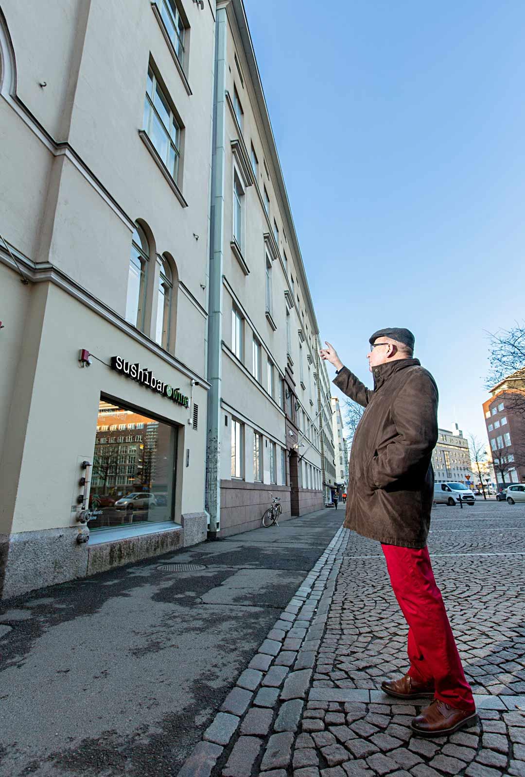 """Emerituspiispa Eero Huovinen näyttää toisen kerroksen ikkunat, joiden takana oli ensin äidin ja myöhemmin myös hänen kotinsa. """"Se oli Malminkadun kotiteatteri, jossa äiti oli ohjaaja sekä veljeni Matti ja minä päänäyttelijöitä."""""""