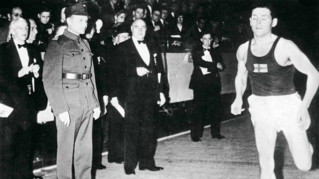 Asepukuinen Paavo Nurmi seurasi tyytyväisenä sivulla Taisto Mäen voittessa sisäratakilpailun Madison Square Gardenin radalla.