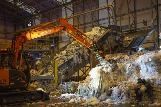 Muovi nostetaan työkoneella linjastolle, josta ne jatkavat matkaansa pesuun. Ennen pesua niistä erotellaan metallit, joita paalien kiinnityksestä on voinut jäädä.