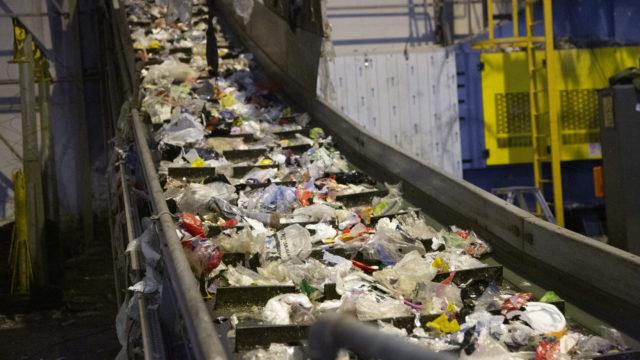 Muovin kierrätyksen ensimmäinen vaihe on syöttö: auki revittyjen muovikassien sisältö leviää linjastolle ja muovi lähtee pitkin lajitteluun.