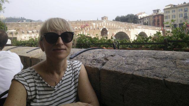 Sanna Kallio kotikaupungissaan Veronassa. Taustalla näkyy Ponte Pietran silta, matkailunähtävyys.Nyt koronapandemia on tyhjentänyt Veronan kadut.