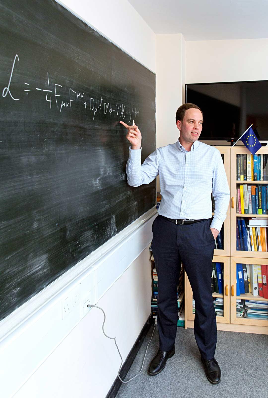 Teoreettisen fysiikan professori Arttu Rajantie kirjoittaa tauluun yksinkertaistetun hiukkasfysiikan standardimallin. Hän vaihtoi ensitöikseen työhuoneensa valkotaulun perinteiseen liitutauluun.