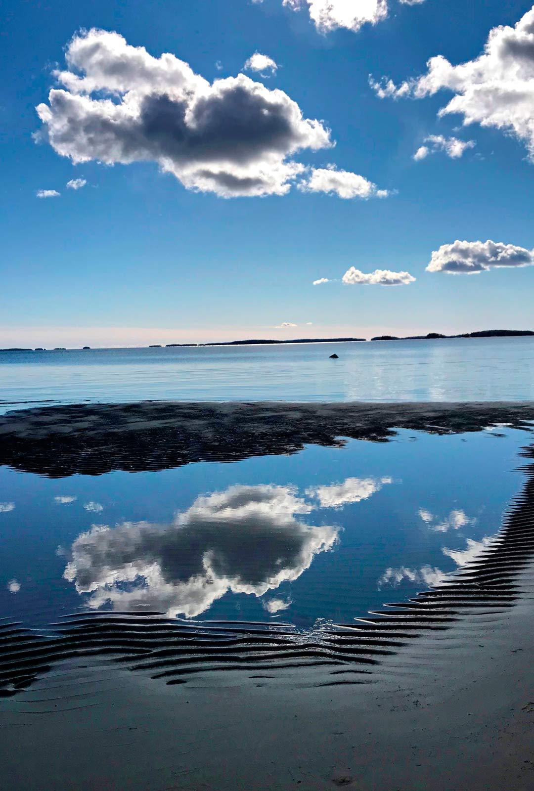 Haminan Pitkienhiekkojen ranta on Johannalle tärkeä. Kuvassa häntä inspiroi sininen taivas pilviheijastuksineen.