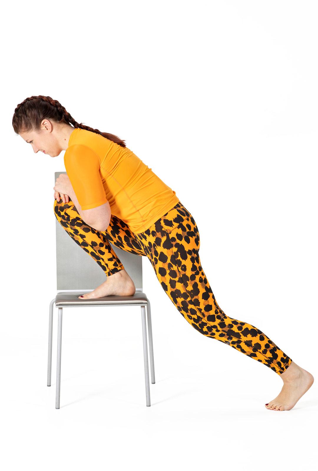Vie paino tuolilla olevan jalan päälle niin pitkälle, että tunnet venytyksen akillesjänteessä.