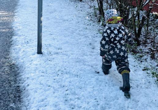 Päiväkotiin matkalla ollut lapsi käveli lumessa perjantaiaamuna Helsingissä.