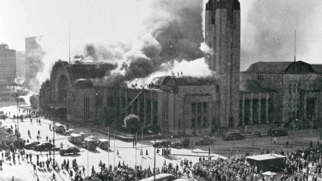 Valokuvan ottohetkellä ryhmä palomiehiä työskenteli vaarallisissa olosuhteissa savua syöksevän asemarakennuksen katolla vuonna 1950.