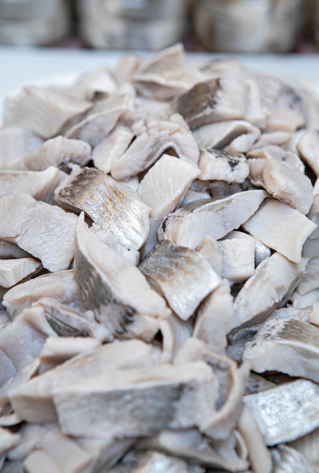 Lasilinjalla sillipalat, tuore sipuli ja muut mausteet asetellaan purkkiin käsin.