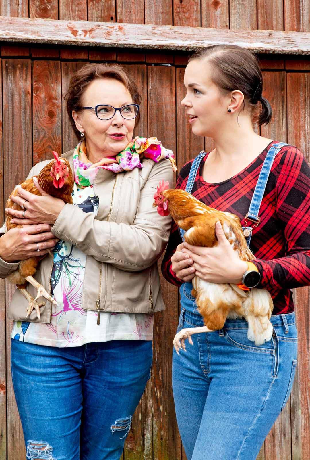 """Kaija Pohjola ja Maria Tyyster kohtasivat kanat, jotka on nimetty heidän mukaansa. Kuningattaret ihmettelevät, miten isäntä Aki Samuli erottaa yhdeksän kanaa toisistaan. """"Mun täytyy ostaa sinulle kaulakoru, että tunnistan. Onpa tämä muuten tosi lämmin"""", Kaija hämmästelee."""