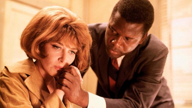 Rikosetsivä Virgil Tibbs (Sidney Poitier) lohduttaa uhrin leskeä rouva Colbertia (Lee Grant) elokuvassa Yön kuumuudessa.