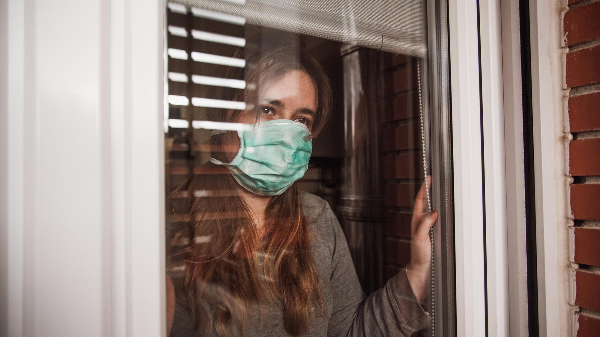 Korona ja karanteeni, nainen ikkunalla maski päällä
